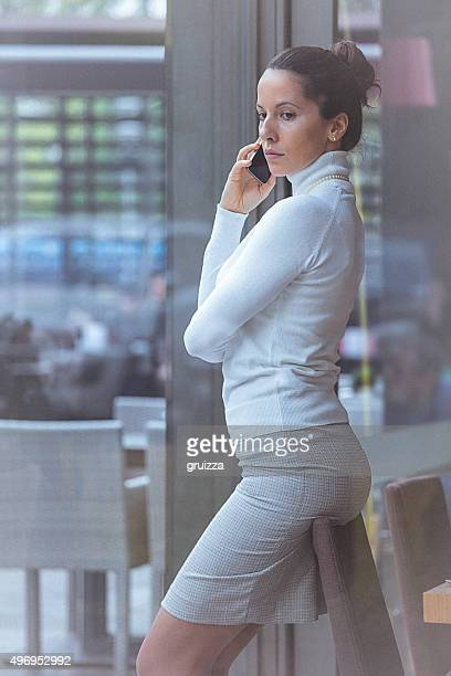Bella donna elegante, presso il cafe, parlando al telefono