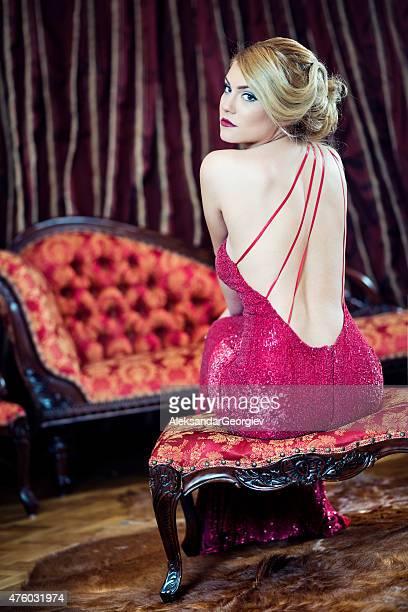 美しいエレガントな女性にポーズを取るソファーにバロック様式のインテリア