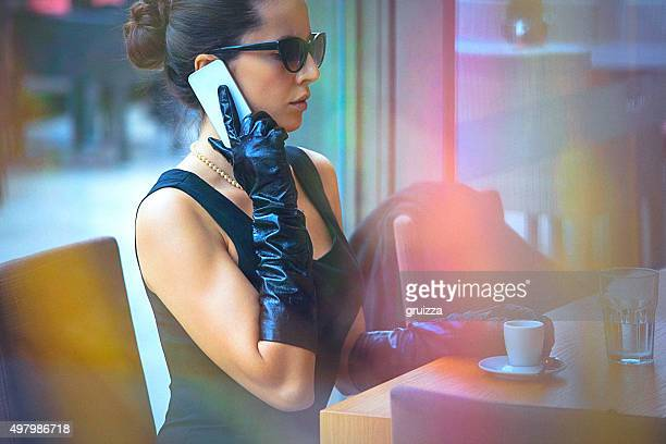Beautiful, elegant woman talking on the mobile phone at cafe