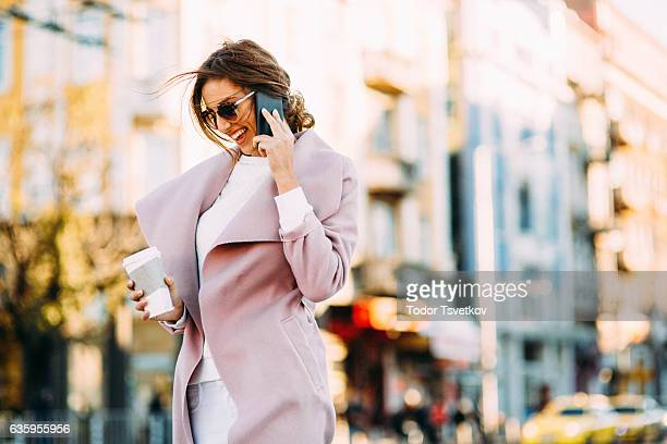 beautiful elegant woman talking on the phone - pink coat stock pictures, royalty-free photos & images