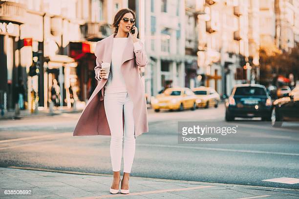 beautiful elegant woman talking on the phone - coat stockfoto's en -beelden