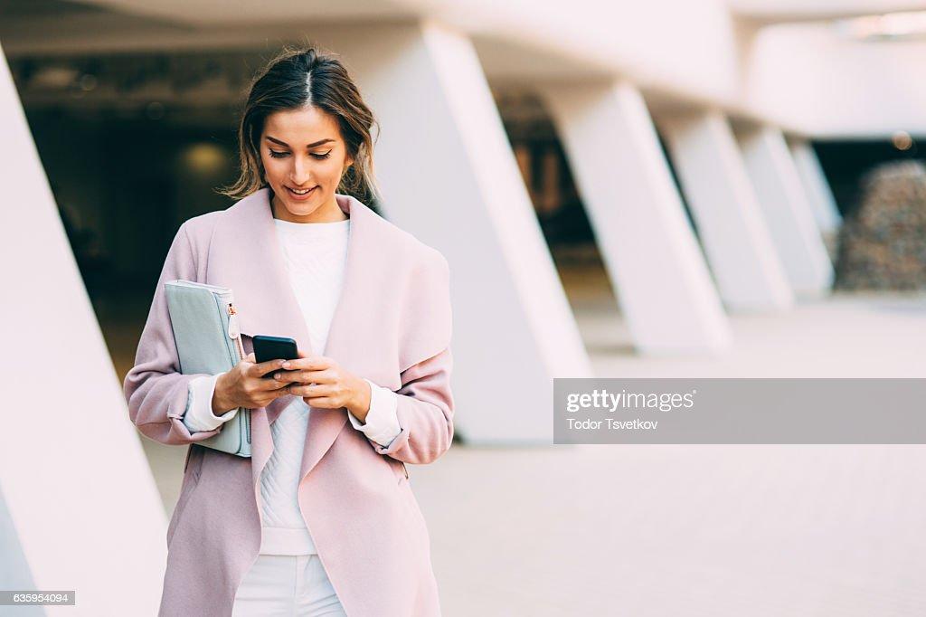 Beautiful elegant woman texting on the phone : Photo