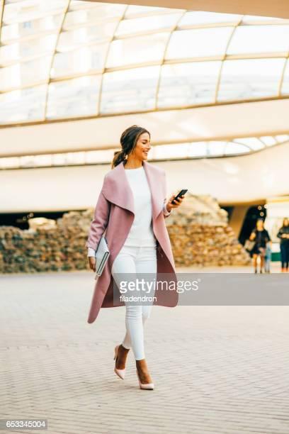 Schöne elegante Frau SMS auf dem Handy