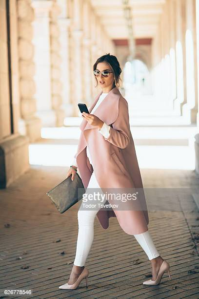 beautiful elegant woman texting outdoors - pink shoe stock pictures, royalty-free photos & images