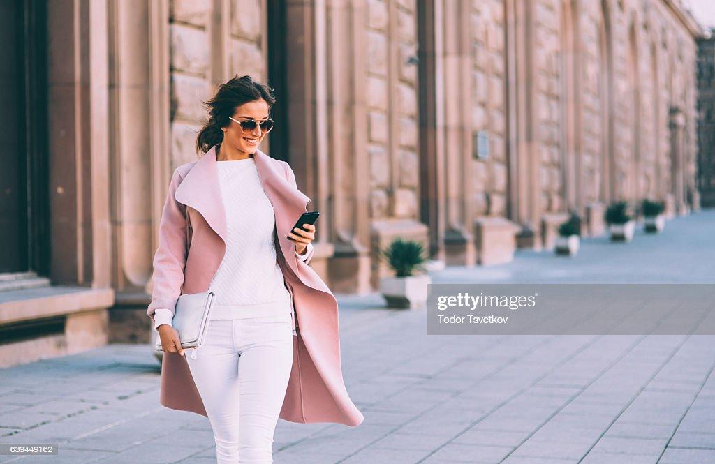 Beautiful elegant woman texting outdoors : Stock Photo