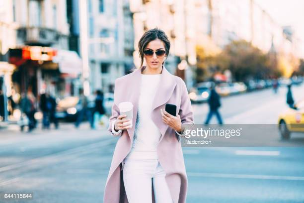 beautiful elegant woman texting outdoors - pink coat stock pictures, royalty-free photos & images