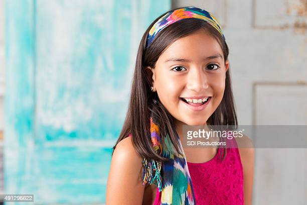 Beautiful elementary age Hispanic girl wearing colorful scarf