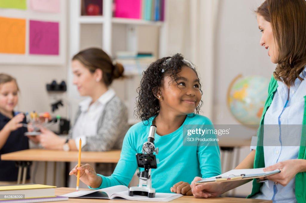 Beautiful Elementary Schoolgirl Talks With Teacher In Class Stock Photo