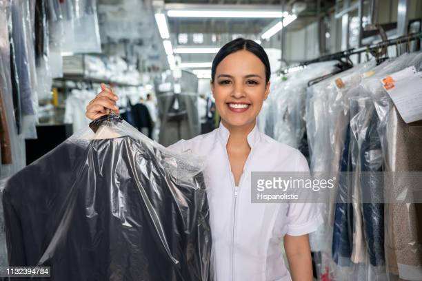 beautiful employee at a laundromat holding a dry cleaned outfit covered with a bag while facing camera smiling - dry cleaned stock pictures, royalty-free photos & images