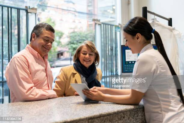 beautiful employee at a laundry service looking for a dry cleaning order on tablet while showing adult customer couple all smiling - dry cleaner stock pictures, royalty-free photos & images