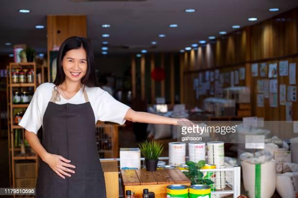 empregado bonito de um mercado orgânico que abre a porta que recebe clientes - cerimônia de boas vindas - fotografias e filmes do acervo