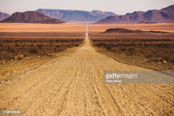 beautiful empty dirt road in desert plain with mountains in background - aiming stock pictures, royalty-free photos & images