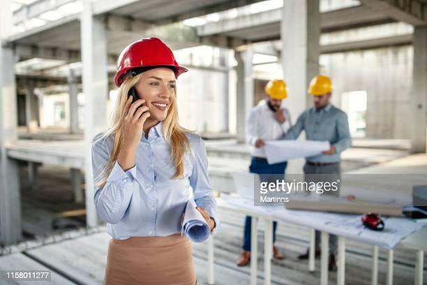 スマートフォンで話す建設現場の美人エンジニア - 女性建築家 ストックフォトと画像