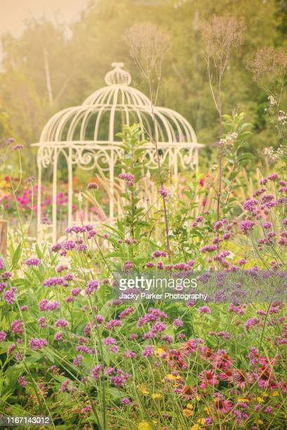 a beautiful english romantic cottage garden with vibrant coloured flowers in the soft summer sunshine with a white wrought iron pergola - gazebo - pergola photos et images de collection