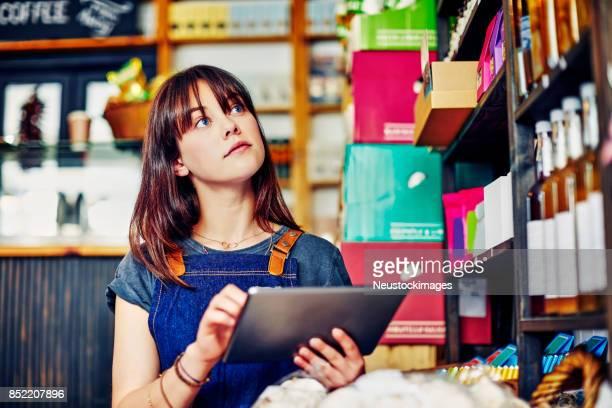 Mooie ondernemer controleren inventaris op digitale Tablet PC in de winkel