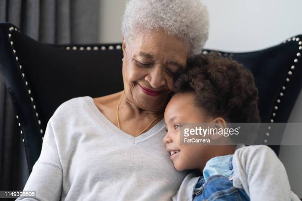 beautiful ethnic grandma is laughing with her young granddaughter. - fat granny stock pictures, royalty-free photos & images