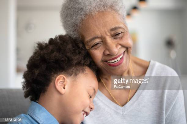 beautiful ethnic grandma is laughing with her young granddaughter. - great grandmother stock pictures, royalty-free photos & images