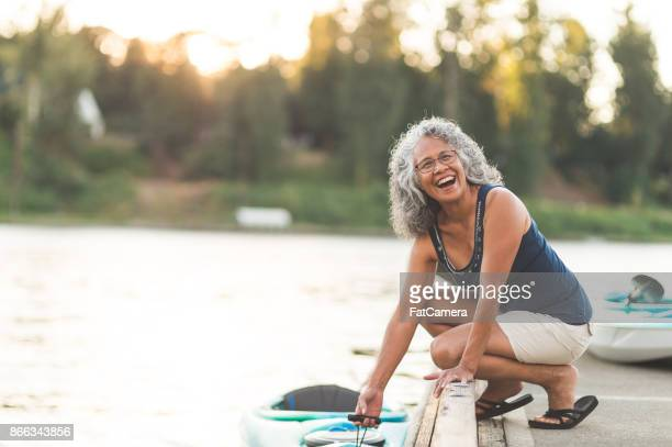 a beautiful ethnic older woman prepares to go kayaking - i love my wife stock pictures, royalty-free photos & images