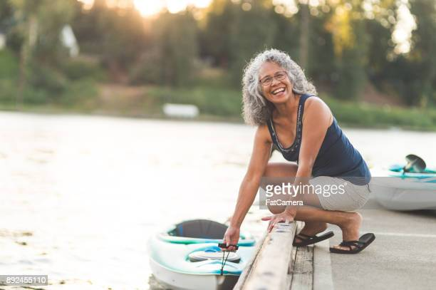 a beautiful ethnic older woman prepares to go kayaking - active senior woman stock photos and pictures