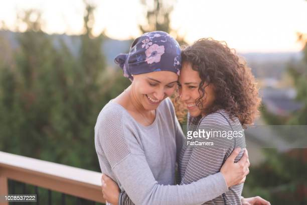 beautiful ethnic woman battling cancer hugs her sister tightly - headwear stock pictures, royalty-free photos & images