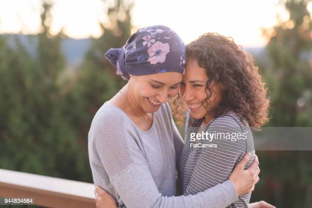 Beautiful ethnic woman battling cancer hugs her sister tightly
