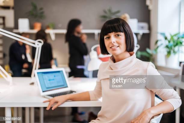 mooie europese onderneemster die in gedeeld bureau werkt, die in team na covid-19 sluiting werkt - 30 34 jaar stockfoto's en -beelden