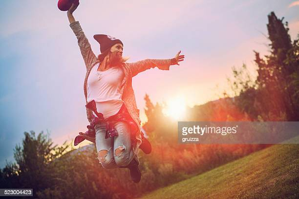 Beautiful excited hipster girl jumping in the courtyard