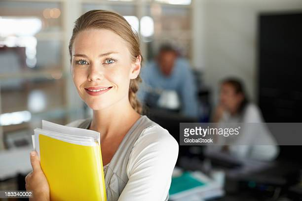 beautiful executive holding folder with colleagues in background - administrative professionals stock pictures, royalty-free photos & images