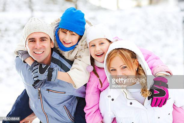 Beautiful family enjoying in snow and winter.
