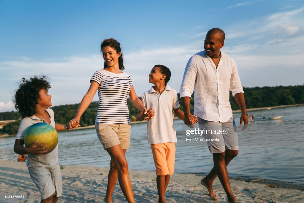 Beautiful family holding hands walking on the beach : Stock Photo