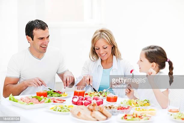 Belle famille de trois appréciant le dîner.