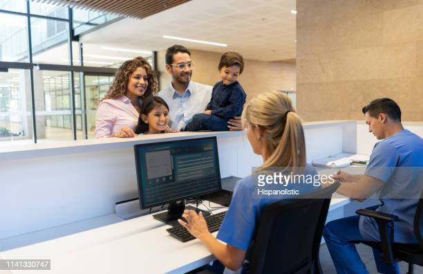 beautiful family registering for a doctor's appointment at the clinic front desk - medical receptionist uniforms stock photos and pictures