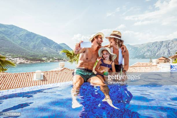 beautiful family take selfie in a swimming pool - vacations stock pictures, royalty-free photos & images