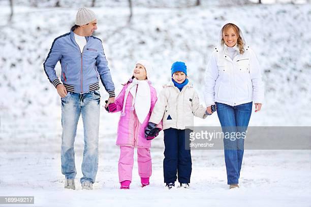 Belle famille marche dans le parc en hiver.
