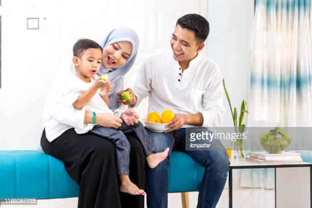 beautiful family with one child eating fruits - malaysia stock pictures, royalty-free photos & images