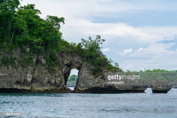 Beautiful famous rock with a hole in Crystal beach with calm waves and crystal clear water in Nusa Penida in Bali, Indonesia.