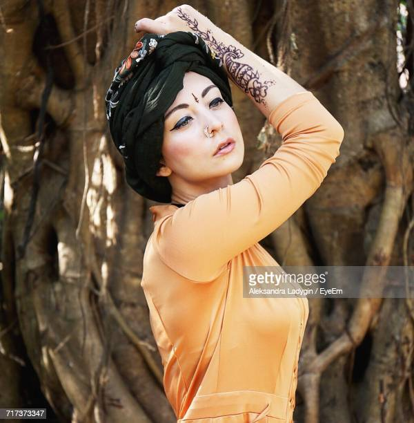 beautiful fashion model posing against tree trunk - bindi stock pictures, royalty-free photos & images