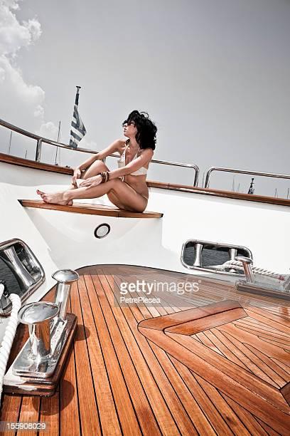 Beautiful fashion model sunbathing and posing on luxury yacht