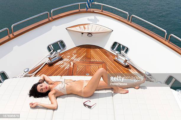 beautiful fashion model sunbathing and relaxing on a luxury yacht - luxury yacht stock pictures, royalty-free photos & images
