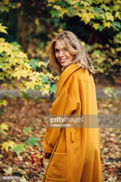 Beautiful Fashion Model wearin Coat in Autumn Park