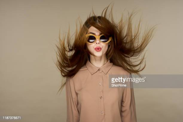beautiful fashion woman in round glasses with a surprised expression, flying hair - brown hair ストックフォトと画像