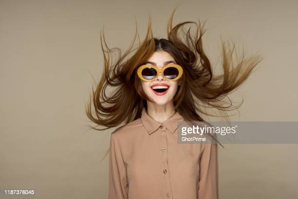 beautiful fashion woman in round glasses with a surprised expression, flying hair - perfectie stockfoto's en -beelden