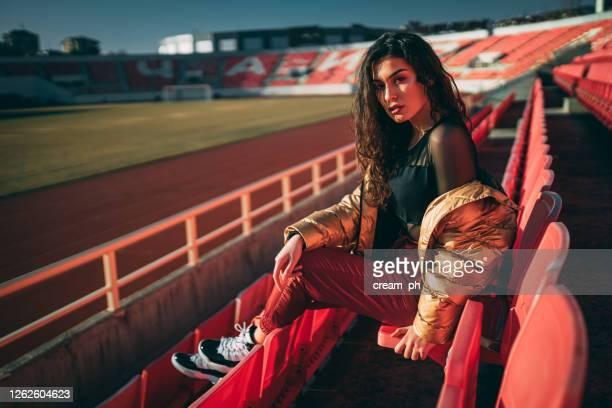 beautiful fashionable young women sitting in a stadium - audience free event stock pictures, royalty-free photos & images