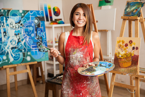 Beautiful female artist in her studio 489243814
