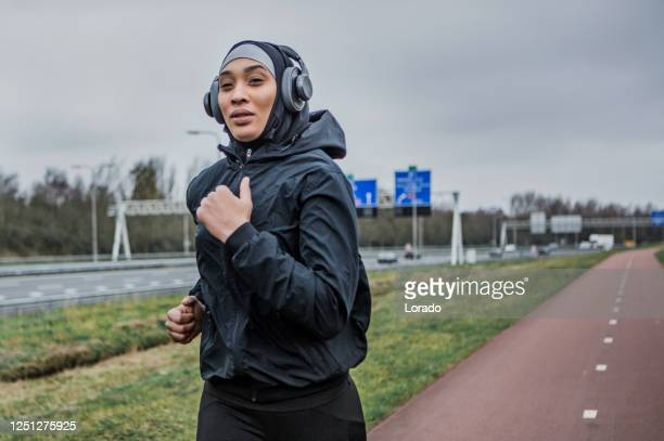 beautiful female athlete wearing a sports hijab - sporting term stock pictures, royalty-free photos & images