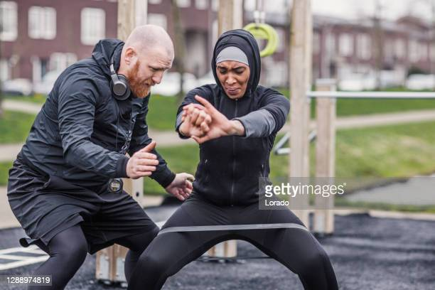 beautiful female athlete wearing a sports hijab with her personal trainer - religious veil stock pictures, royalty-free photos & images
