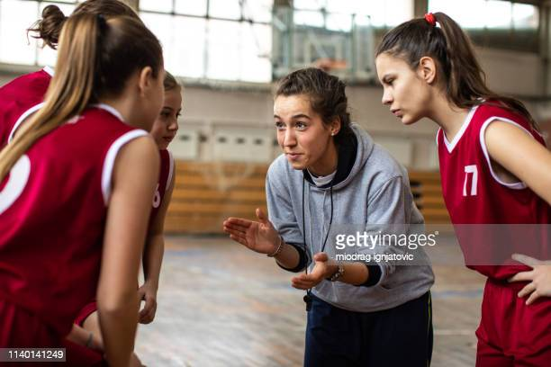 beautiful female coach cheering girls before match - basketball team stock pictures, royalty-free photos & images