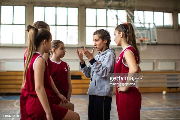 beautiful female coach talking with teenage basketball team - basketball team stock pictures, royalty-free photos & images