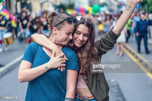 lgbtqiプライドイベントで美しい女性カップル - ゲイプライドのシンボル ストックフォトと画像