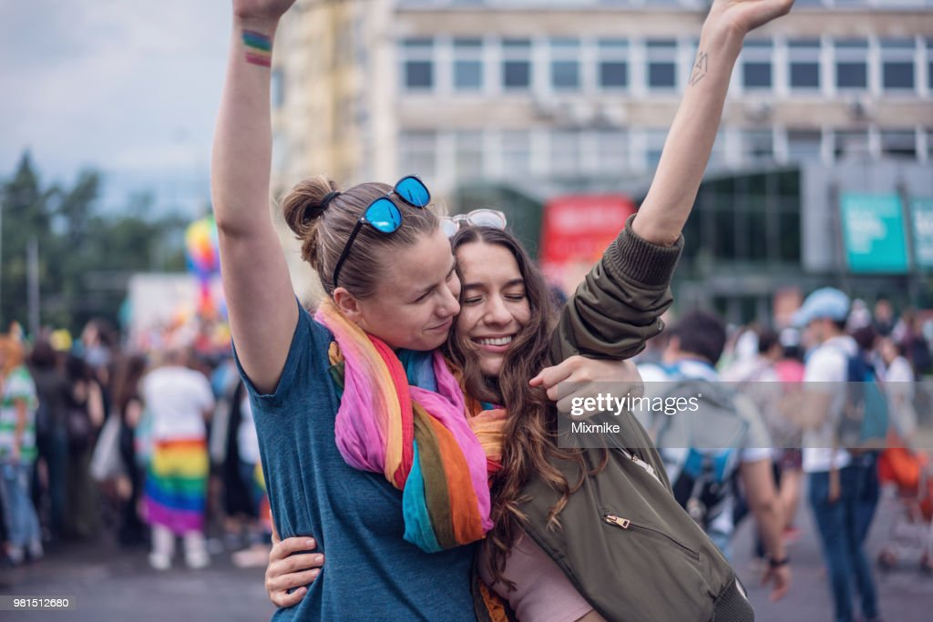 Beautiful female couple hugging while marching on the street : Stock Photo